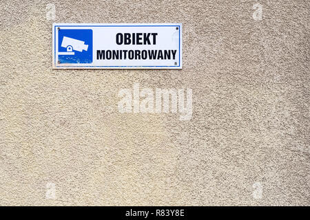 under video surveillance text in Polish, blue CCTV symbol on the wall in Warsaw, Poland - Stock Photo