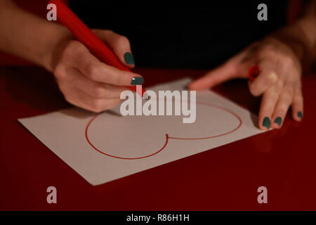 Girl drawing a heart on a white paper with a red marker. Hands with green nail and marker. White paper on a table with drawing. - Stock Photo