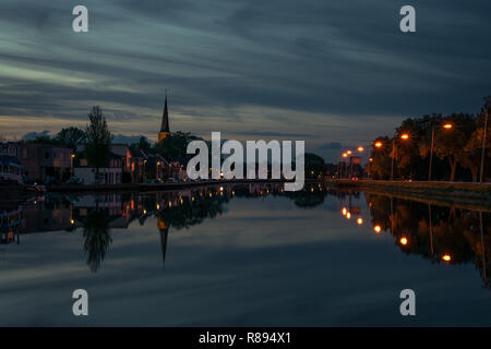 Dutch town with church tower near Gouda with reflections in the water at blue hour. Beautiful scene with perspective an dreamy clouds. - Stock Photo