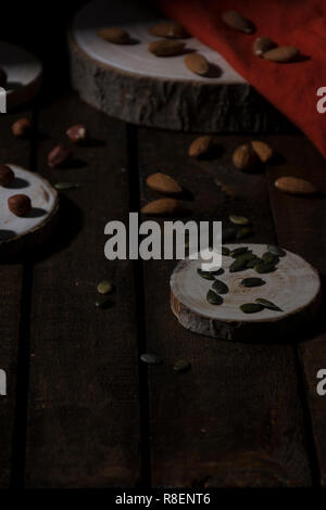 Almonds, hazelnuts and pumpkin seeds on pieces of logs and an orange fabric in dark style - Stock Photo