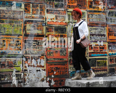 Central, Hong Kong: Tourist poses for photograph in famous Graham Street,  with artwork by Alex Croft as background - Stock Photo