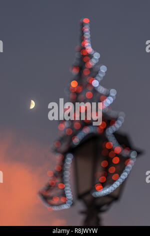 VILNIUS, LITHUANIA - DECEMBER 26, 2017:  The moon and illuminated Christmas decoration on a lantern during sunset at the Town Hall Square, Baltic - Stock Photo
