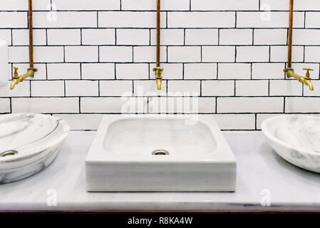 Marble sink in a public restroom with retro golden water tap with copper pipes on wall with white tiles, front view with room for text - Stock Photo