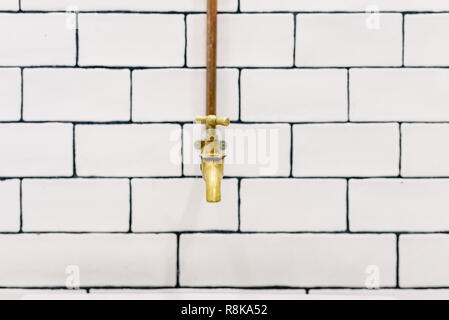 front view with space for text, Retro golden water tap with copper pipes on wall with white tiles - Stock Photo