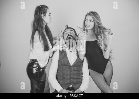 female hairdresser is cutting hair of bearded man - Stock Photo