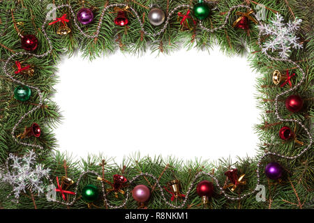 Christmas frame made of fir branches decorated with bells and balls isolated on white background - Stock Photo