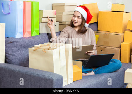 Young Asian female entrepreneur online seller, wearing Christmas hat, working on her online business at home, checking out boxes of her Christmas prod - Stock Photo