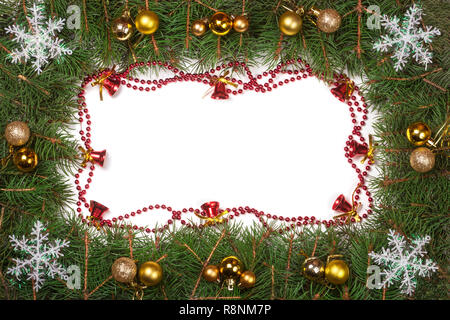 Christmas frame made of fir branches decorated with balls bells and snowflakes isolated on white background - Stock Photo