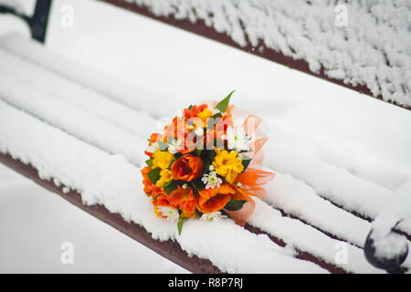 Bridal bouquet and lilies on a bench in the snow in the winter - Stock Photo