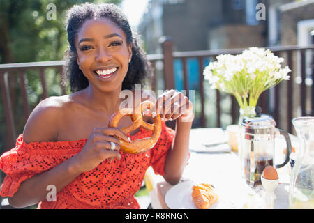 Portrait smiling, confident young woman with pretzel enjoying breakfast on sunny balcony - Stock Photo
