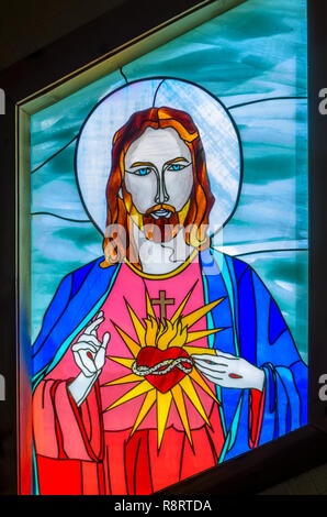 A stained glass window featuring Jesus is one of the highlights at Chapel of Mercy in Greenwood, Mississippi. - Stock Photo