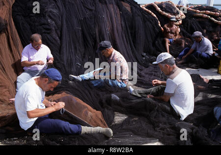 Fishermen repairing fishing nets on quayside, Olhao, Algarve, Portugal, Europe - Stock Photo