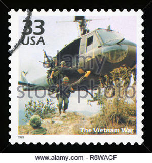 UNITED STATES OF AMERICA - CIRCA 1999: A postage stamp printed in USA showing an image soldiers jumping from a military helicopter during the Vietnam - Stock Photo