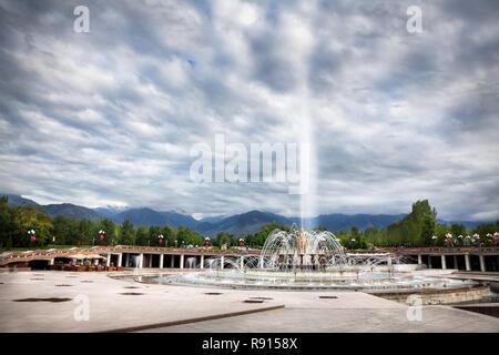 Big fountain at dramatic overcast sky in dendra park of first president Nursultan Nazarbayev in Almaty, Kazakhstan - Stock Photo