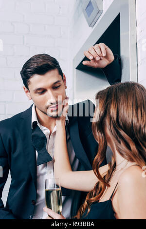 woman holding champagne glass and touching face of man while waiting for elevator - Stock Photo