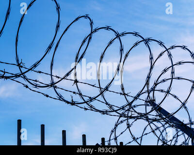 Razor wire against blue sky and clouds. - Stock Photo