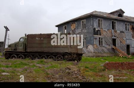 AT-T caterpillar all-terrain vehicle in front of a derelict house in a rural locality, Dalniye Zelentsy, Kola Peninsula - Stock Photo