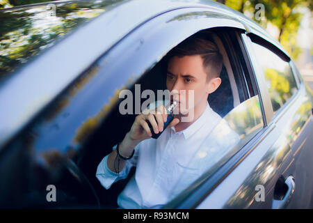 View from side young man smoking an e-cigarette as he drives his car on an urban street. car driver peeps out of the car and smokes - Stock Photo
