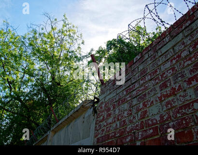 barbed wire over brick fence in spring, Moscow - Stock Photo