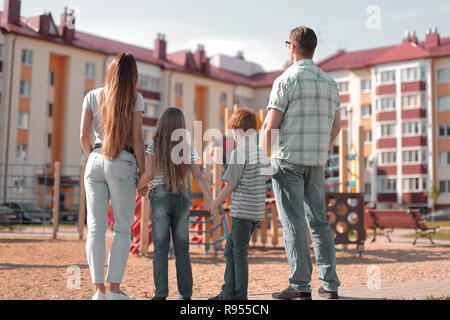 rear view.a young family is looking at a new apartment building - Stock Photo