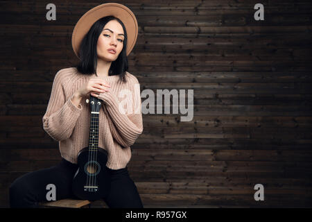 Young hipster girl having fun and posing with small ukulele guitar on a wooden studio background. - Stock Photo