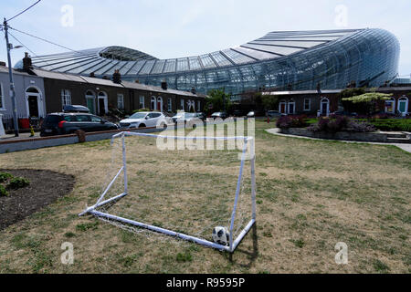 Small football playground with a ball in the goal. In the background the huge Aviva Stadium can be seen above the houses. Dublin, Ireland. - Stock Photo