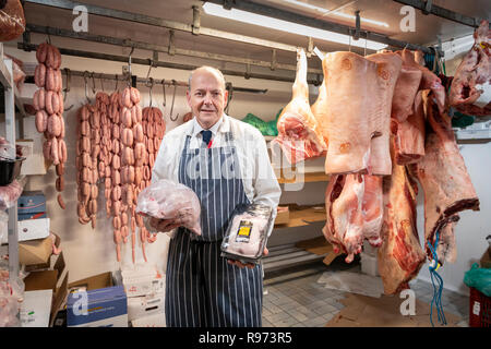 Willingham, Cambridgeshire, UK, 21st December 2018.  Butcher Steve Collett starts the day early to prepare the Christmas meat orders at the traditional village Highgate Butchers shop. Turkeys and beef and other products are stored in cold rooms then assembled into individual orders ready for the weekend rush when customers will collect for the festive season. Credit: Julian Eales/Alamy Live News - Stock Photo