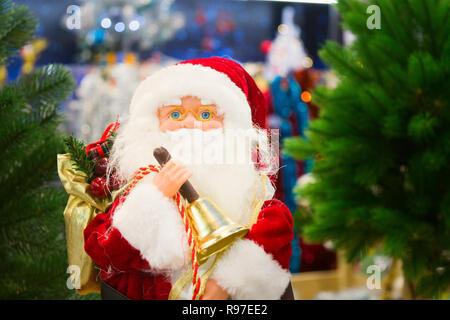 Toy Santa Claus standing in shop with New Year decoration, soft focus - Stock Photo