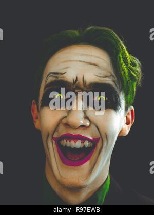 Bloody Halloween theme: The crazy face on black background. Copy space for text. - Stock Photo