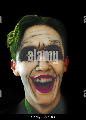Bloody Halloween theme: The crazy joker face on black background laughing in the dark. Halloween holidays. - Stock Photo
