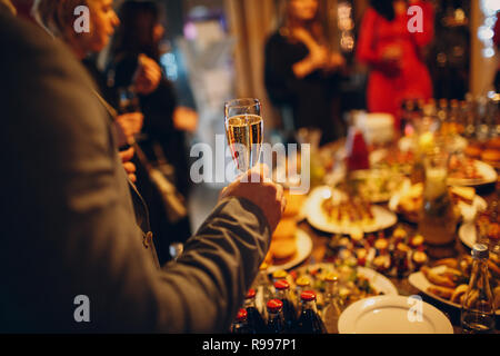 Catering festive concept. Man holds a glass of champagne on celebration table with food background. - Stock Photo