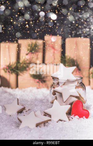 Gingerbread Christmas cookies stars in the glass jar and christmas decorations on wooden background with snow. Copy space. - Stock Photo