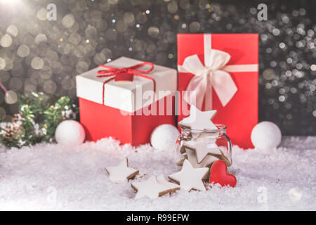 Gingerbread Christmas cookies stars in the glass jar and gifts in the background with snow. Copy space. - Stock Photo