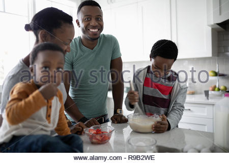 Portrait happy young family baking in kitchen - Stock Photo