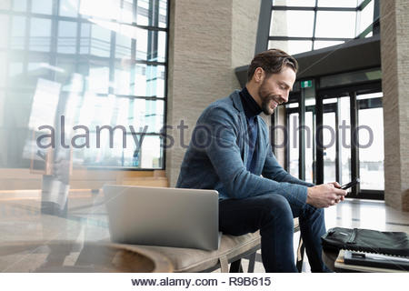 Businessman with laptop using smart phone in lobby - Stock Photo