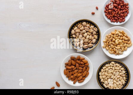 Corner border of an assorted variety of fresh nuts in individual bowls viewed from above on textured white with copy space - Stock Photo