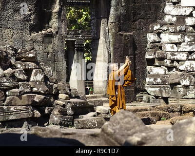 A Buddhist monk is taking pictures at the beautiful Angkor Wat in Siem Reap, Cambodia. - Stock Photo
