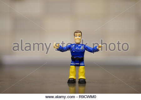 Poznan, Poland - December 22, 2018: Fireman Sam toy figure with open arms standing on a wooden table in soft focus.  - Stock Photo