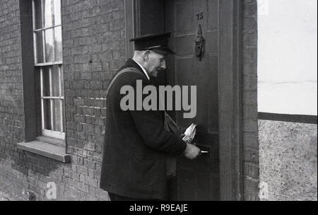1940s, a Royal Mail postman delivering post through a front door letter box of a victorian terraced house, England, UK - Stock Photo