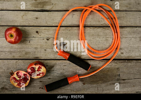 jumping rope and fruit on wooden background. - Stock Photo