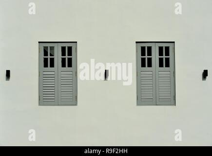 Front view of traditional vintage Singapore shop house exterior with antique grey wooden shutters isolated on a pale grey wall - Stock Photo