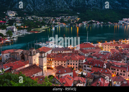 Red roof houses and boats on the Adriatic coast in the Bay of Kotor at dusk, Montenegro - Stock Photo