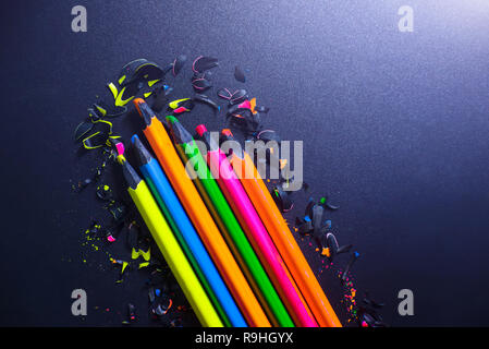 Bright colored abstraction on a dark background. Chips of crayons. - Stock Photo