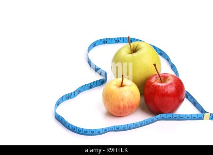 Loosing weight weighing scale and eating healthy in the new year starting with a delicious apple - Stock Photo