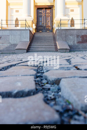 View from low point on pavement stones on front of church with door. Floor close up. - Stock Photo