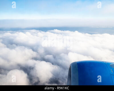 view of aircraft turbine over dense clouds in blue sky during flight through porthole - Stock Photo