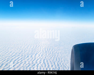 view of blue sky over dense cloudy surface through aircraft porthole during flight - Stock Photo