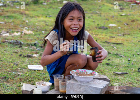 Thakhek, Laos - April 19 2018: Local child playing to eat a meal with mud taken from a river in a remote rural area of Laos - Stock Photo