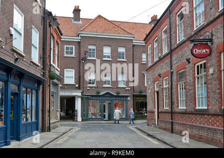 Old brick buildings housing shops and restaurants on alley of Back Swinegate in historic district of City of York, England, UK - Stock Photo