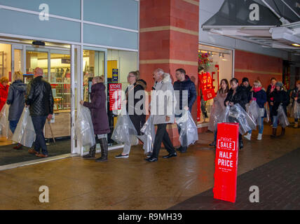 Southport, Merseyside, UK.  26th December 2018. 6am Start for Sales at Next as queues form for high street discounts and post Christmas bargains.  People queuing at some stores were issued with large clear plastic bags to contain their purchases, and make their 'half price' sale items visible to in store supervisors. Shoppers will always expect a manic experience trying to get to the Next Boxing Day sale in stores. Credit: MediaWorldImages/AlamyLiveNews. - Stock Photo